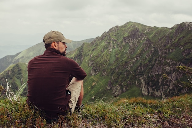 観光、山、ライフスタイル、自然、人々の概念-日没時に夏の山の崖の上に立って、自然の景色を楽しむ若い男