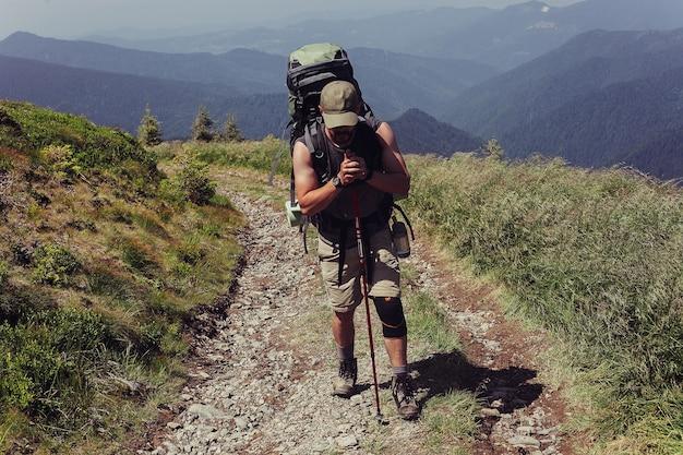 Туризм, горы, образ жизни, природа, люди, концепция селфи - медицинский костыль и фиксированная нога обездвиживают достигнутую горную вершину. мужчина зафиксировал сломанную ногу иммобилайзером сильфона человека. весенний солнечный день