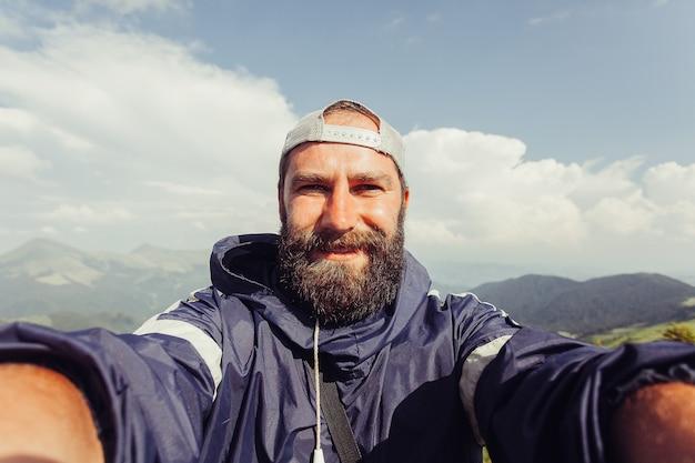 観光、山、ライフスタイル、自然、人々、selfieの概念-若い男の旅行者は夏の日没時に背景の山でselfieを作ります。ひげを生やした観光客の笑顔。スローモーション、テクノロジー