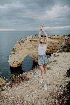 Turismo in portogallo, europa. turista femminile biondo di stile di vita sulle rocce dell'arenaria