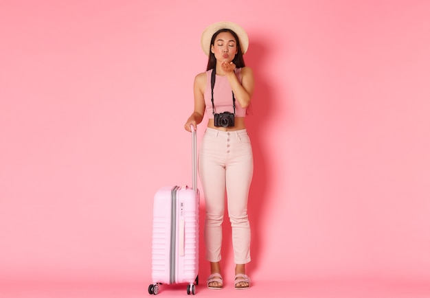 관광, 여름 휴가, 휴가 해외 개념. 어리 석고 귀여운 아시아 여자 관광의 전체 길이, 가방, 분홍색 벽으로 서, 공기 키스를 보내는 여름 옷 여행자.