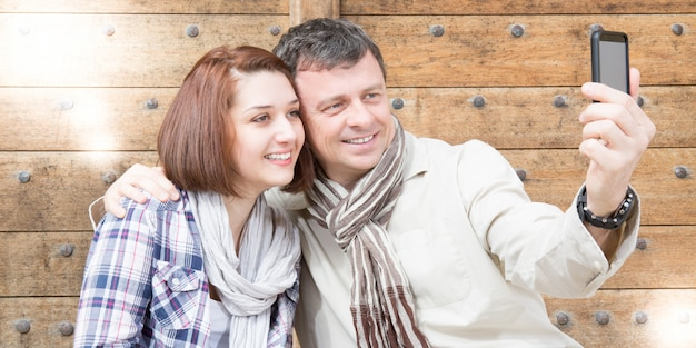 Tourism and technology smiling couple making selfie photo