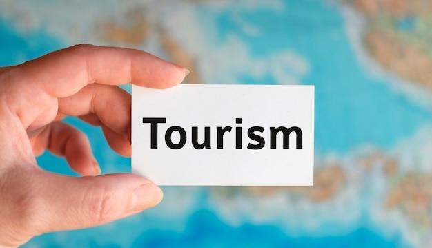 Туризм - текст на белом листе с глобусом на фоне карты атласа