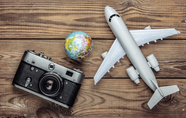 Tourism and travel concept. globe, camera and passenger plane figurine on wooden tabe. top view. flat lay
