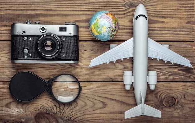 Tourism and travel concept. globe, magnifier, camera and passenger plane figurine on wooden table. top view. flat lay