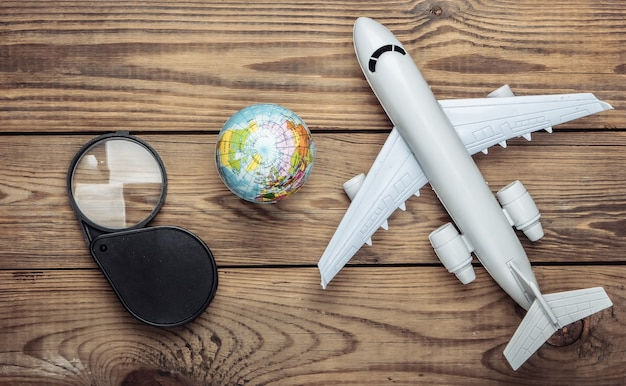 Tourism and travel concept. globe, magnifier and passenger plane figurine on wooden table. top view. flat lay