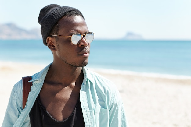Tourism, travel, leisure, lifestyle and adventure. attractive stylish dark-skinned traveler dressed in trendy clothes enjoying beautiful seascape during nice walk on urban beach early in the morning