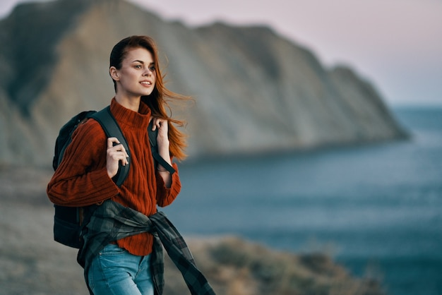 Tourism travel women in sweater with backpack on the back and mountains in the background. high quality photo