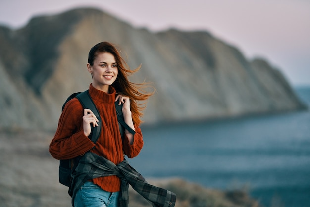 Tourism travel women in sweater with backpack on the back and mountains in the background