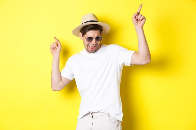 観光、旅行、休日のコンセプト。休暇を楽しんでいる男性観光客、麦わら帽子とサングラスで踊り、指を横向きにしています。