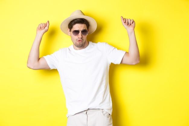 観光、旅行、休日のコンセプト。休暇を楽しんで、麦わら帽子とサングラスで踊り、黄色の背景にポーズをとる男性観光客。