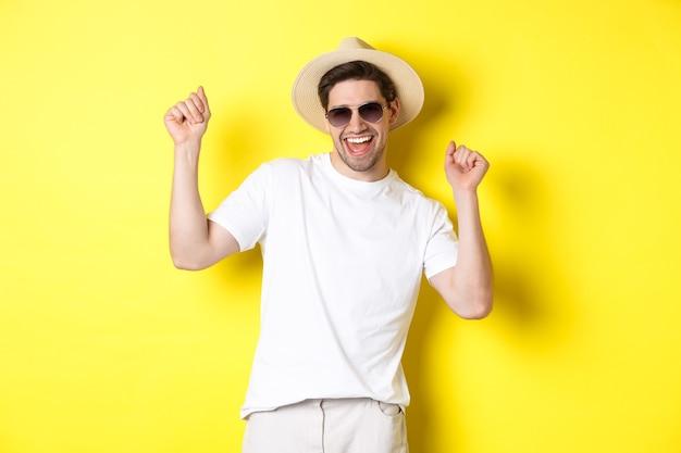 Concetto di turismo, viaggi e vacanze. felice ragazzo caucasico che balla e si diverte in vacanza, indossando occhiali da sole con cappello di paglia, in piedi su sfondo giallo.