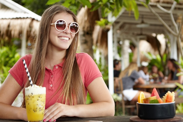 Tourism and vacations. beautiful young caucasian lady sitting at bar counter with glass of smoothie and fruit bowl, smiling cheerfully
