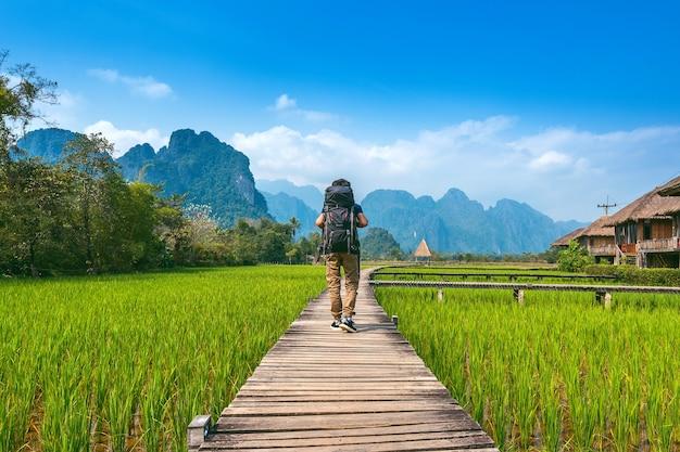 ラオスのヴァンヴィエンの木製の小道をバックパックで歩く観光。