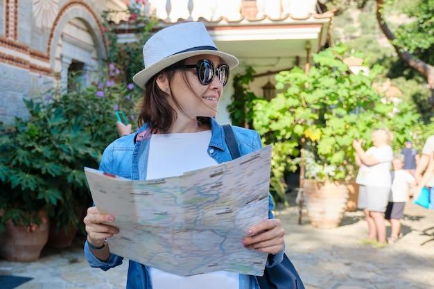 観光、キリスト教の修道院を訪れる女性、山の中のギリシャの歴史的建造物、地図付きの女性