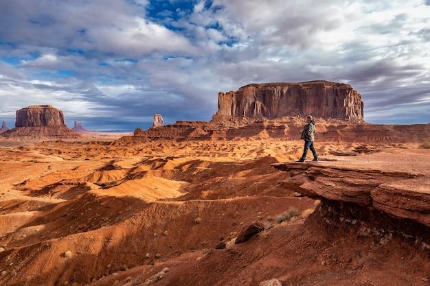 米国アリゾナ州モニュメントバレーの背景に嵐のある景色を眺める観光客。