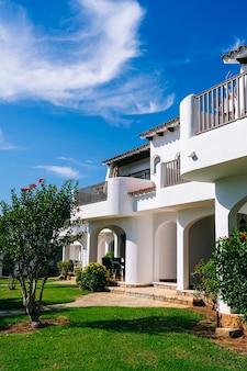 Туристические апартаменты с белым фасадом, зеленой травой и голубым небом в солнечный день