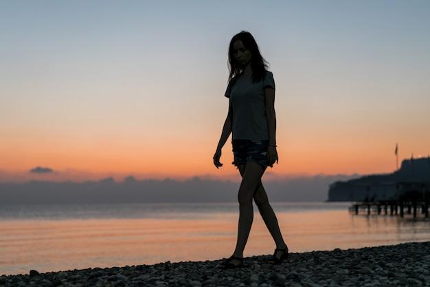 Турист на рассвете гуляет по песку