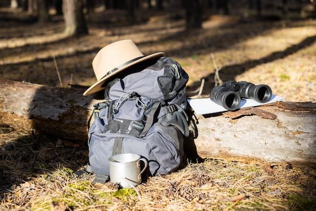 관광 배낭, 모자, 쌍안경 및 숲의 로그에지도