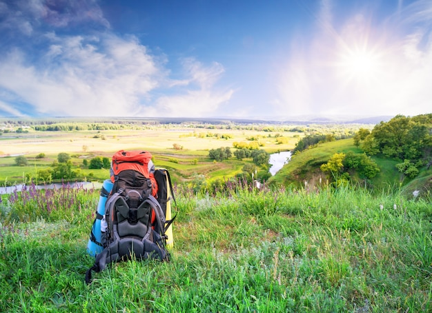 Tourist backpack on hill in green grass under bright sun