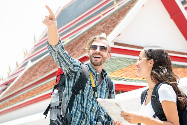 Tourist backpackers traveling in ancient thai temple on vacations in thailand