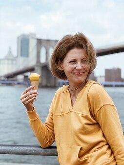 맨해튼 고층 빌딩과 브루클린 다리에서 아이스크림 콘을 먹고 관광 아름 다운 여자. 예쁜 젊은 여자는 디저트를 먹는다. 휴가에 음식 개념