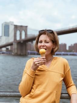 Туристическая красивая женщина ест рожок мороженого