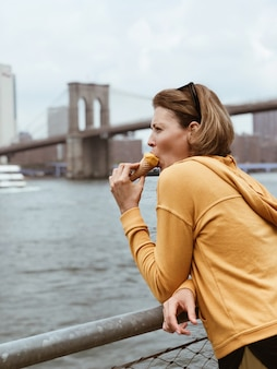 Tourist beautiful woman eating a cone of ice cream. pretty young woman eats dessert. food concept on vacation