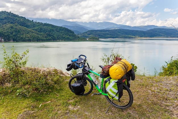 Tourist bicycle stands on the bank of the river in the background of mountains, vietnam