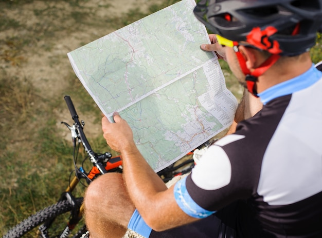 Tourist bicyclist with route map looking to the map
