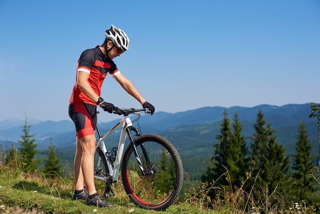 Турист байкер, глядя на свой велосипед на горном холме