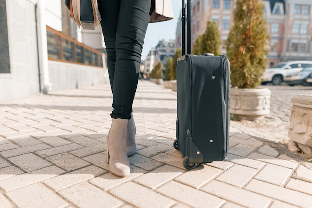 Tourist black suitcase and woman's legs