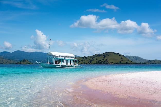 Туристическая лодка в прозрачной воде на розовом пляже в национальном парке комодо