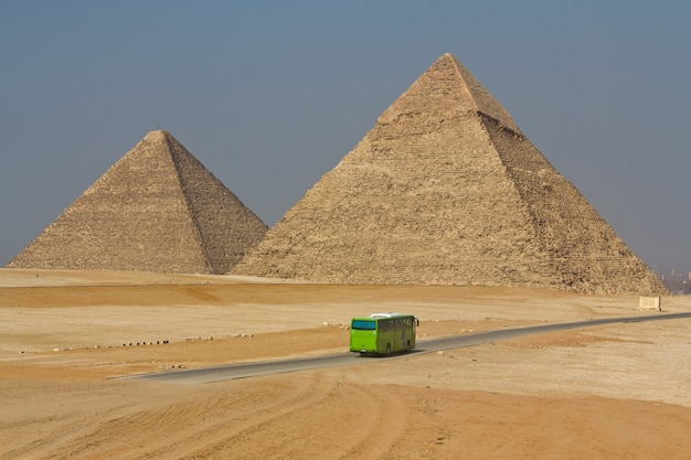 Tourist bus and egyptian pyramids