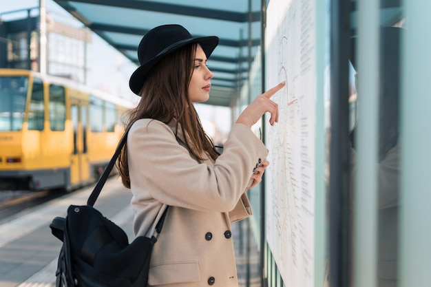 Tourist at bus stop looking on map