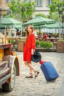 美しい赤いジャケットを着た観光ビジネスの若い女性が街の通りでスーツケースを引っ張っています
