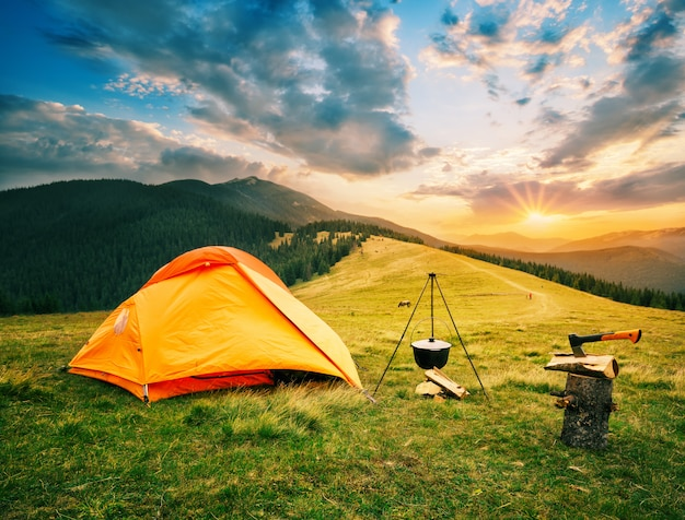 Tourist camp in mountains with tent and cauldron over fire at sunset