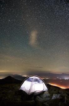 별이 빛나는 밤하늘 아래 산 꼭대기에 관광 캠프