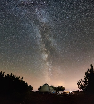 Tourist camp on the top of mountain under night starry sky