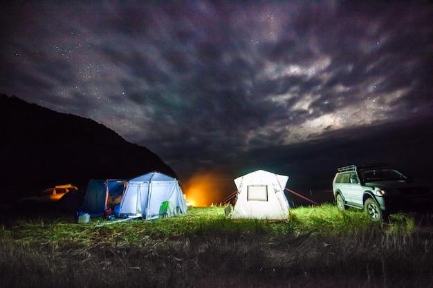 Туристический кемпинг на берегу моря ночью под пасмурным небом. имеется некоторый шум от высокого iso