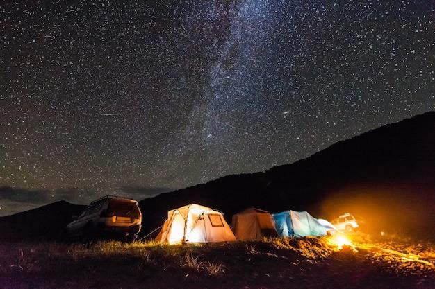 Туристический кемпинг на морском побережье ночью под звездным небом. имеется некоторый шум от высокого iso