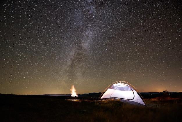 밤 별이 빛나는 하늘 아래 산에서 캠핑 관광