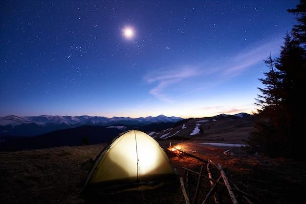 山の森の近くでキャンプする観光客。星と月でいっぱいの夕方の空の下で照らされたテントとキャンプファイヤー