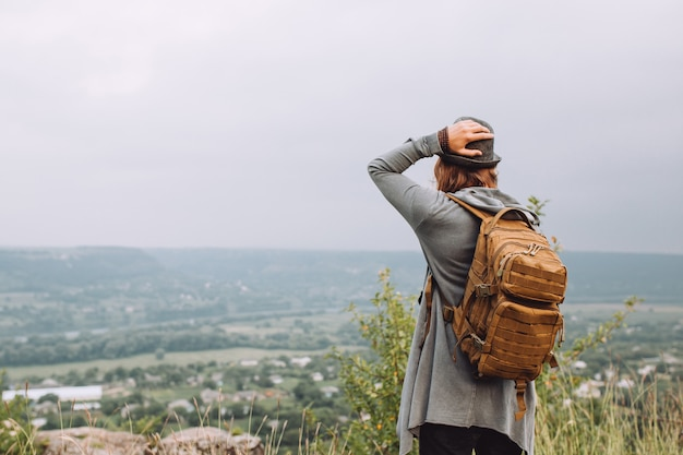 大きなバックパックを背負って山に歩く観光客