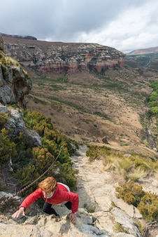 Tourist climbing cliff in the golden gate highlands national park, south africa