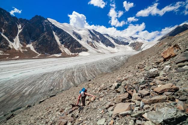 A tourist climbs to the top of the bolshoy aktru glacier, altay, russia. high quality photo