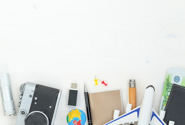 Tourist composition with travel accessories on a white wooden surface