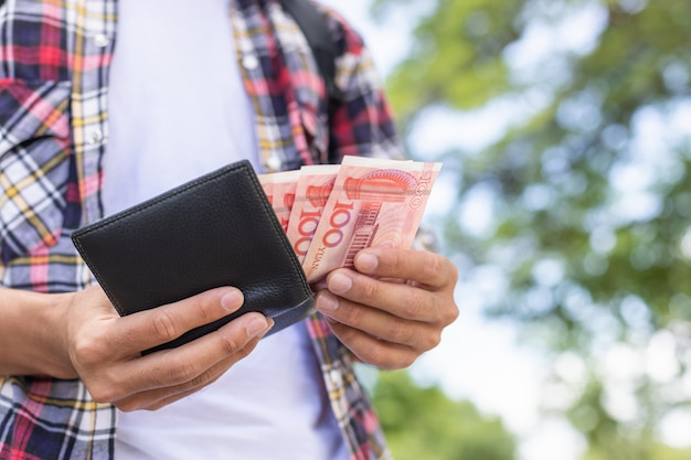 Tourist counting or checking banknote in black wallet that he found in tourist attraction