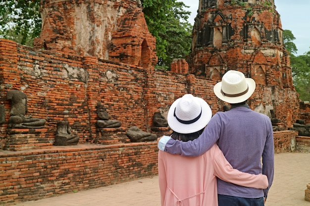 Tourist couple admiring a group of headless buddha images in ayutthaya historical park, thailand