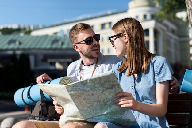 Tourist couple on bench consulting map